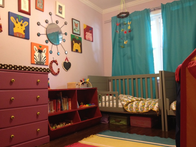 Toddler-eye view of the other side. My husband built the red toy shelf, the changing table was a dresser found by the side of the road, my dad painted the square animal paintings, and most of the other art are actually cards we got at baby showers or repurposed art from other rooms.